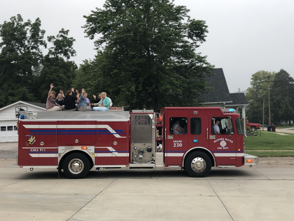 Elementary staff riding to school on firetruck