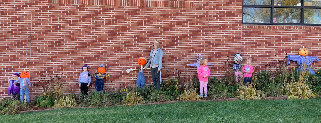 Mrs. Burch and preschoolers with their scarecrows.